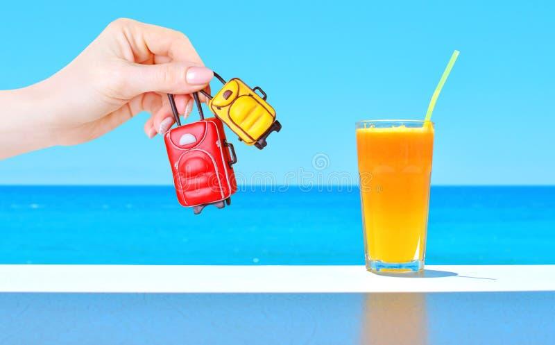Bagaglio miniatura del giocattolo in mano femminile e succo fresco arancio in un vetro sulla tavola con il contesto blu del mare fotografia stock libera da diritti