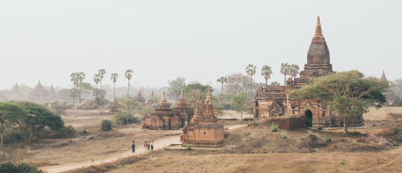 Bagan, Мьянма - март 2019: люди идя через древние храмы и пагоды на заходе солнца стоковые изображения