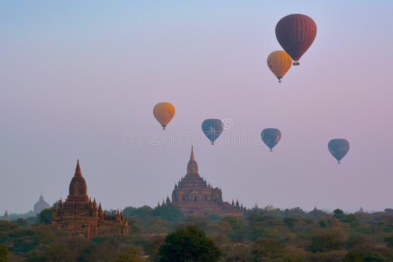 BAGAN, MYANMAR - 18 DE FEBRERO DE 2016: Globos de aire caliente sobre volar sobre los templos y las pagodas de Bagan foto de archivo