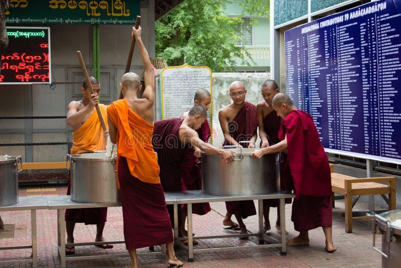 Bagan, Myanmar - 24 de julho de 2014: As monges burmese locais estão cozinhando r imagens de stock