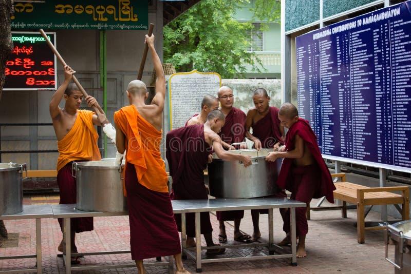 Bagan, Myanmar - 24 de julho de 2014: As monges burmese locais estão cozinhando r imagem de stock royalty free