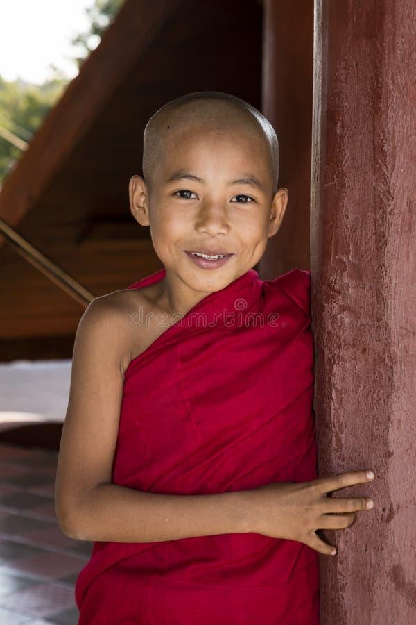 Bagan, Myanmar, 29 December, 2017: De jonge Boeddhistische beginner kijkt ongunstig achter een rode pijler royalty-vrije stock afbeeldingen