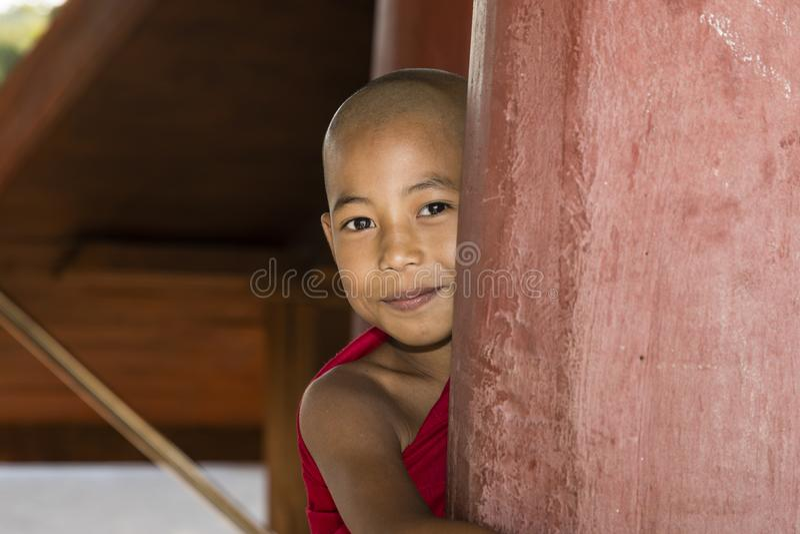 Bagan, Myanmar, 29 December, 2017: De jonge Boeddhistische beginner kijkt ongunstig achter een rode pijler royalty-vrije stock foto's