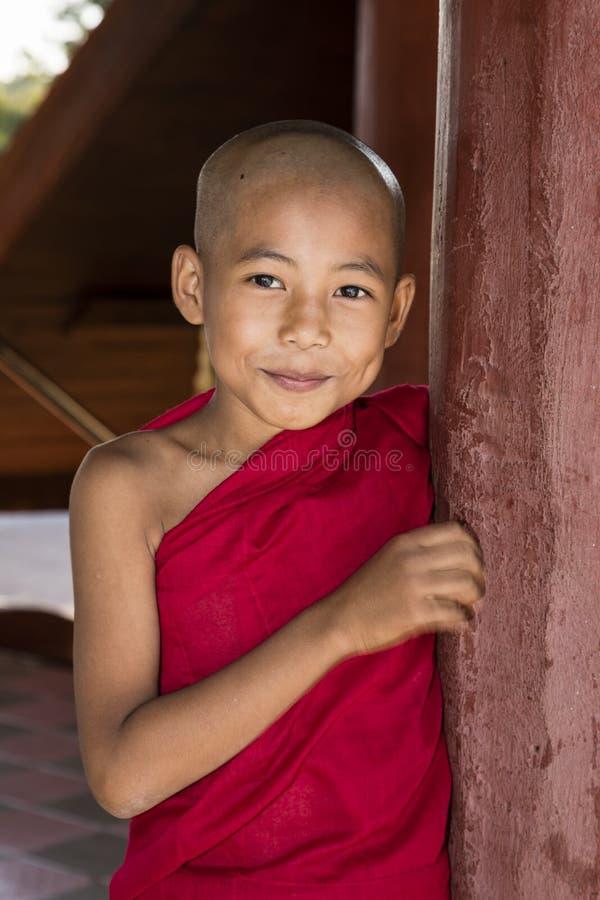 Bagan Myanmar, December 29, 2017: Den unga buddistiska novisen ser mischievously bak en röd pelare i en pagod i Bagan royaltyfri fotografi