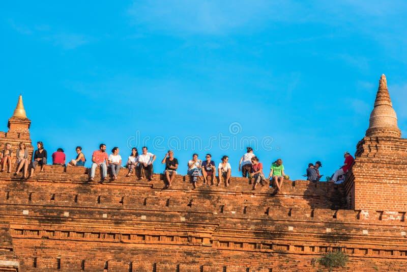 BAGAN MYANMAR - DECEMBER 1, 2016: Folket sitter överst av en pagod Kopiera utrymme för text royaltyfri fotografi