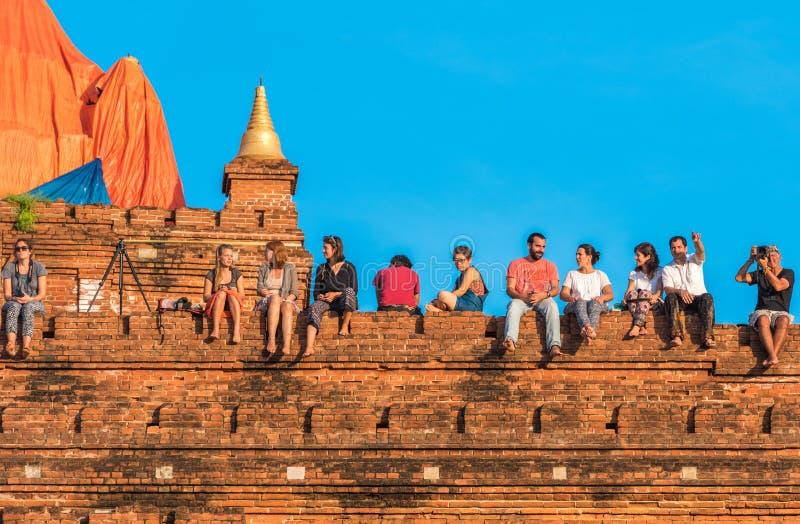 BAGAN MYANMAR - DECEMBER 1, 2016: Folket sitter överst av en pagod Kopiera utrymme för text arkivfoto