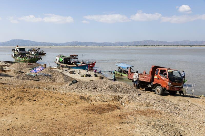 Bagan, Myanmar, am 27. Dezember 2017: Arbeitskräfte laden Sand auf Schiff an der Anlegestelle stockfoto