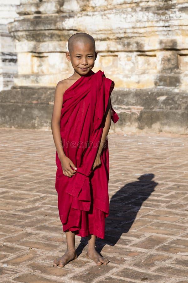 Bagan, Myanmar, am 29. Dezember 2017: Junger buddhistischer Anfänger steht mit seiner roten Robe vor einer Pagode stockbilder