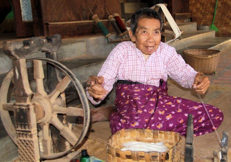 BAGAN, MYANMAR - 21 DICEMBRE 2015: Uomo birmano anziano che fila davanti ad una capanna semplice con la ruota di legno antica immagine stock libera da diritti