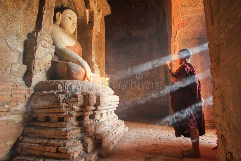 BAGAN, MYANMAR - em maio de 2016: Velas ardentes da monge na frente da estátua da Buda dentro do pagode em maio de 2016 em Bagan imagem de stock