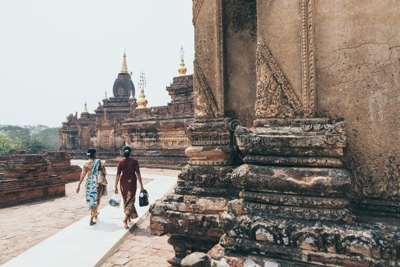Bagan, Myanmar - em março de 2019: Duas mulheres em vestidos tradicionais que andam ao lado do templo budista de Bagan, Myanmar fotografia de stock royalty free