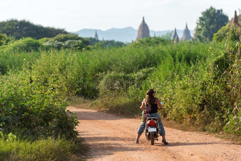 BAGAN MYANMAR, GRUDZIEŃ, - 1, 2016: Kobieta na motocyklu na tle wiejski krajobraz Odbitkowa przestrzeń dla teksta zdjęcia royalty free
