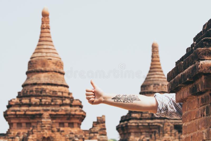 Bagan, Myanmar - Maart 2019: hand met tatoegering van tempels en pagoden van oude Bagan op de achtergrond stock afbeelding