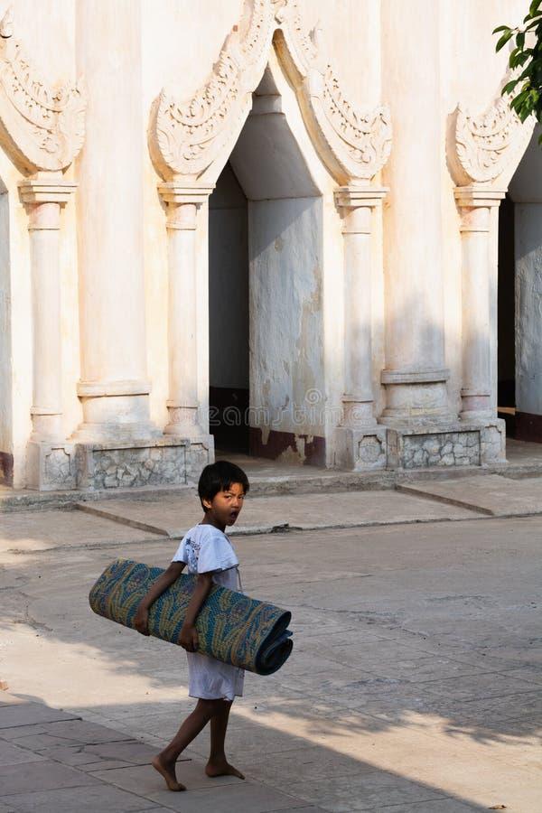 Bagan, Myanmar - Maart 2019: Kind die gerolde bamboemat in Bagan dragen stock foto's