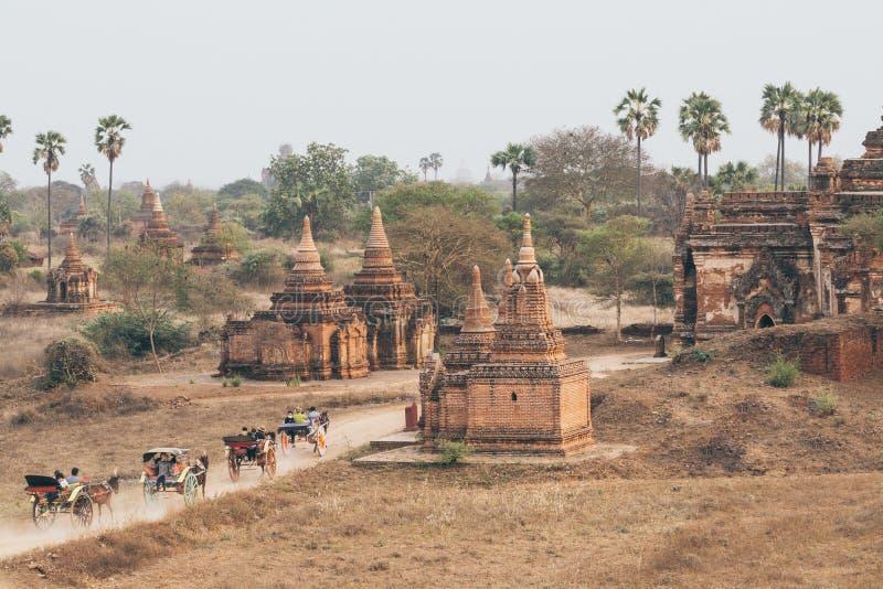 Bagan, Myanmar - Maart 2019: paardvervoer die toeristen drijven door oude tempels en pagoden stock afbeelding