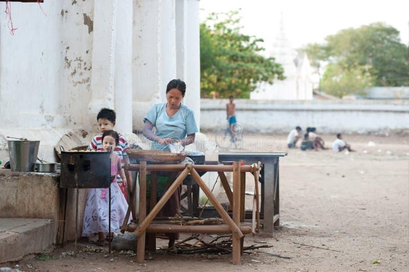 BAGAN, MYANMAR - 3 MAGGIO: Il venditore femminile produce una tagliatella per il cliente fotografie stock libere da diritti