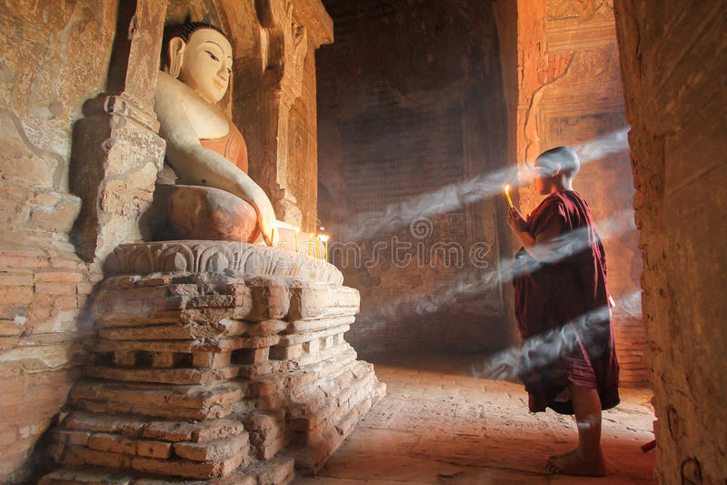 BAGAN, MYANMAR - Mai 2016: Brennende Kerzen des Mönchs vor Buddha-Statue innerhalb der Pagode im Mai 2016 in Bagan stockbild