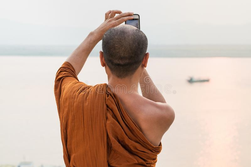 Bagan, Myanmar - March 2019: Burmese Buddhist monk in orange robe taking pictures of Irrawaddy river at sunset royalty free stock image