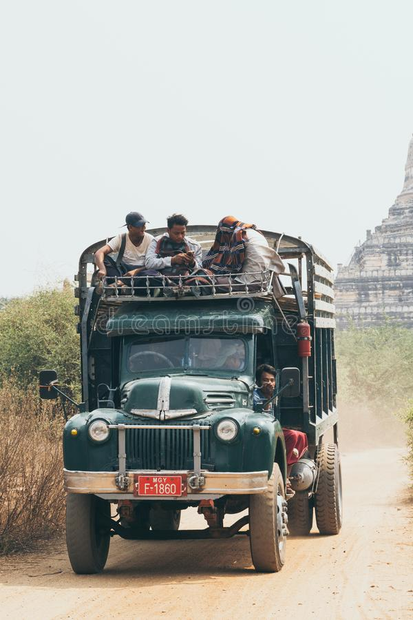 Bagan, Myanmar - March 2019: Burmese men riding retro truck next to Buddhist temple stock images