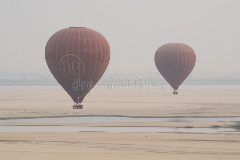 Bagan, Myanmar - March 2019: hot air balloons landing near Irrawaddy river. At sunrise, fly, over, pagoda, temple, ancient, sky, ballooning, luxury, view stock image