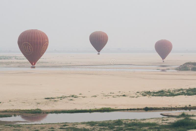Bagan, Myanmar - March 2019: hot air balloons landing near Irrawaddy river royalty free stock photos