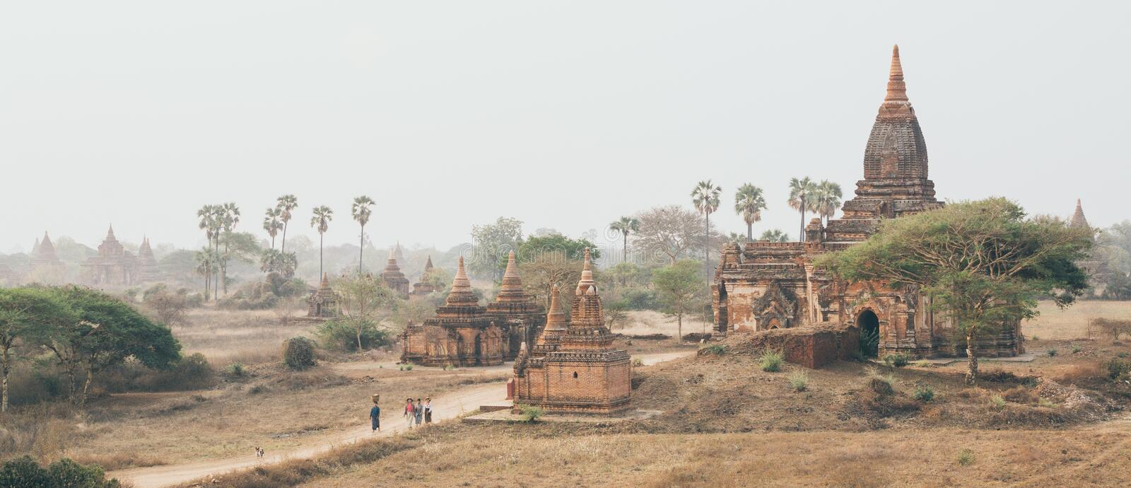 Bagan, Myanmar - March 2019: people walking through ancient temples and pagodas at sunset.  stock images