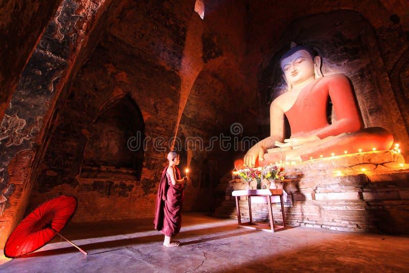 BAGAN, MYANMAR - mayo de 2016: Velas ardientes del monje delante de la estatua de Buda dentro de la pagoda en mayo de 2016 en Bag imagenes de archivo