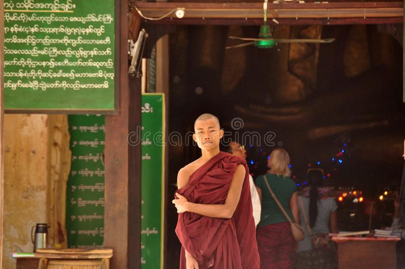BAGAN MYANMAR - NOVEMBER 13, 2015: Etnisk munkstående Ung asiatisk man i ämbetsdräkten av munken som framme står av tempelingånge royaltyfri bild