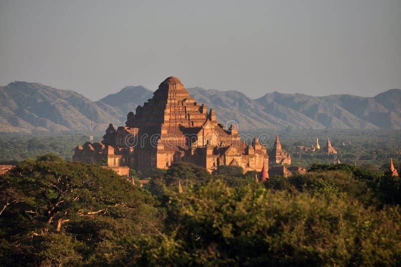 BAGAN, MYANMAR - NOVEMBER 18, 2015: Oude oosterse tempel in groen terrein, Weergeven van mooie steen Dhammayangyi in groen stock foto