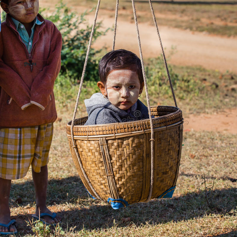 BAGAN, MYANMAR - NOVEMBER 26, 2014: an unidentified Burmese child is transported by the mother in a basket in the fields among t stock photography