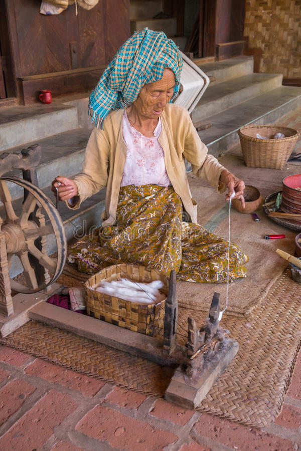 BAGAN, MYANMAR - NOVEMBER 28, 2014: an unidentified elderly woman burnese produces cotton with traditional instruments in a villa. Ge of Bagan stock photos