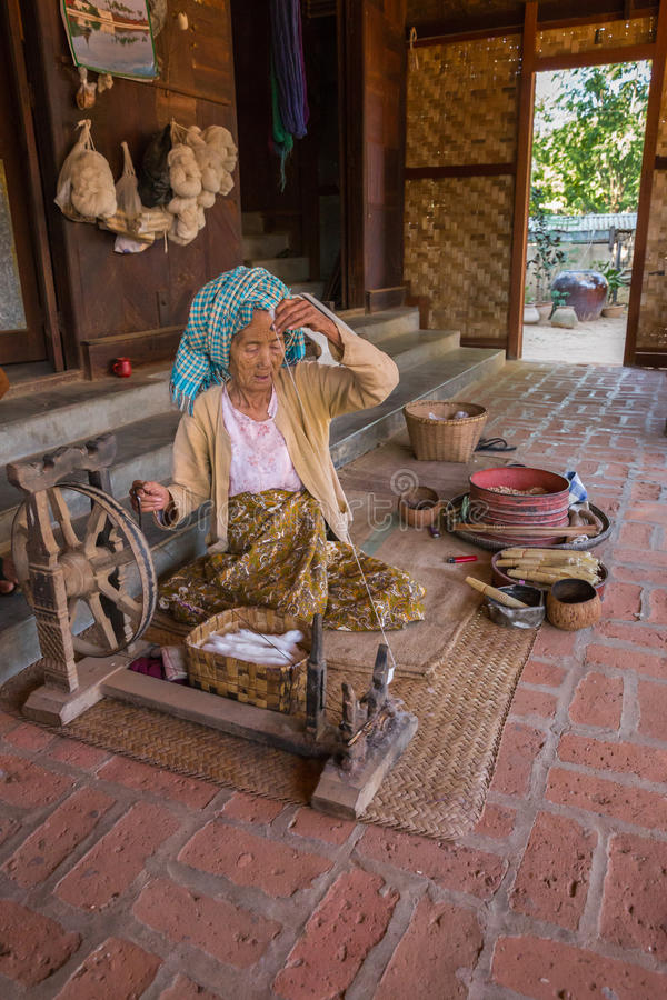 BAGAN, MYANMAR - NOVEMBER 28, 2014: an unidentified elderly woman burnese produces cotton with traditional instruments in a villa. Ge of Bagan royalty free stock image