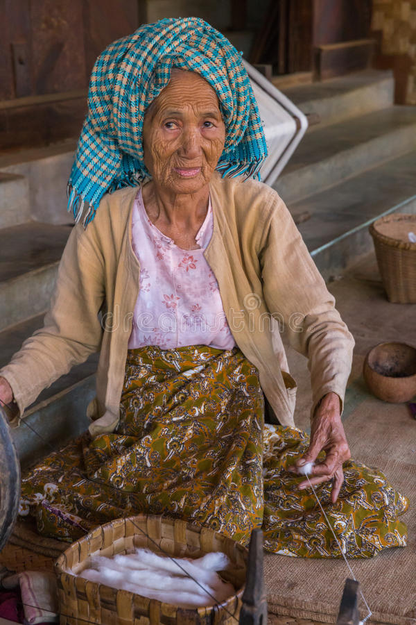 BAGAN, MYANMAR - NOVEMBER 28, 2014: an unidentified elderly woman burnese produces cotton with traditional instruments in a villa. Ge of Bagan royalty free stock photos