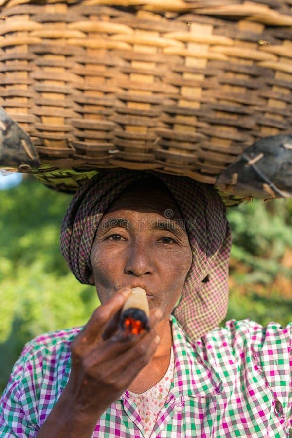 Unidentified burmese woman smoking a traditional big tobacco cigar. Bagan, Myanmar - October 11, 2016: Unidentified burmese woman smoking a traditional big stock images