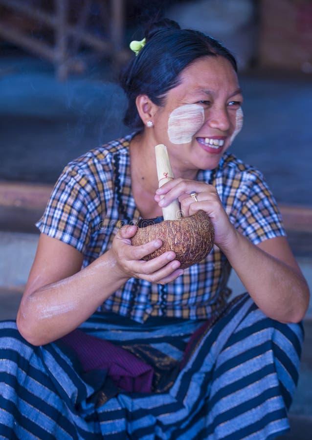 Burmese woman smoking a cheroot cigar. BAGAN, MYANMAR- SEP 04 : Woman smoking a cheroot cigar in market in bagan, Myanmar on September 04, 2017. Cheroot is a royalty free stock image