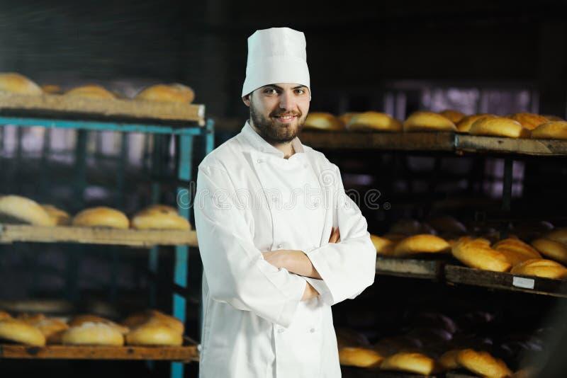 Bagare i den vita likformign på bakgrundsbagerit royaltyfri foto