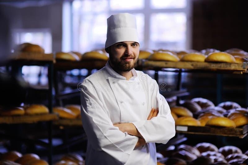 Bagare i den vita likformign på bakgrundsbagerit royaltyfri bild