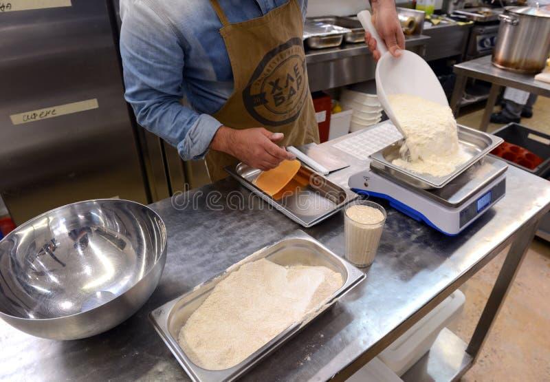 Bagare som gör handgjorda loaves av bröd i ett familjbageri som formar degen in i tradional, formar i Sofia, Bulgarien på Septemb royaltyfria bilder