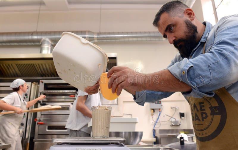 Bagare som gör handgjorda loaves av bröd i ett familjbageri som formar degen in i tradional, formar i Sofia, Bulgarien på Septemb royaltyfri foto