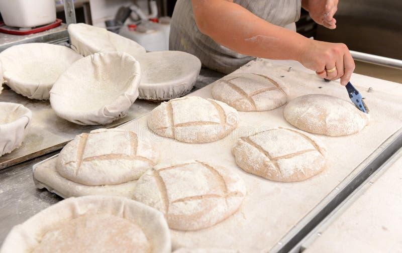 Bagare som gör handgjorda loaves av bröd i ett familjbageri som formar degen in i tradional, formar i Sofia, Bulgarien på Septemb royaltyfri bild