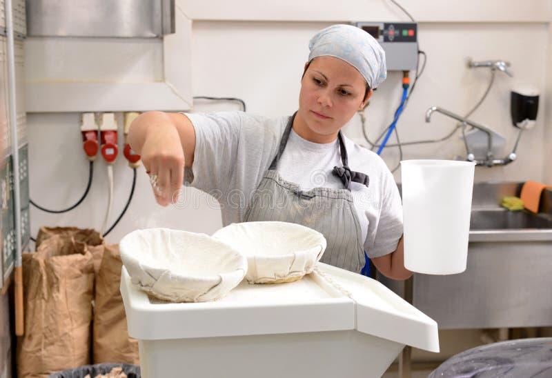 Bagare som gör handgjorda loaves av bröd i ett familjbageri som formar degen in i tradional, formar i Sofia, Bulgarien på Septemb royaltyfri fotografi
