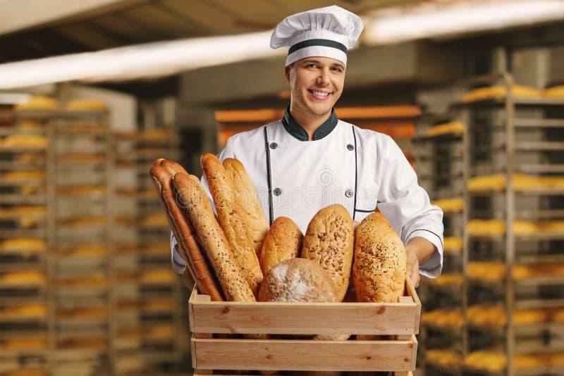 Bagare som mycket rymmer en korg av bröd arkivbild