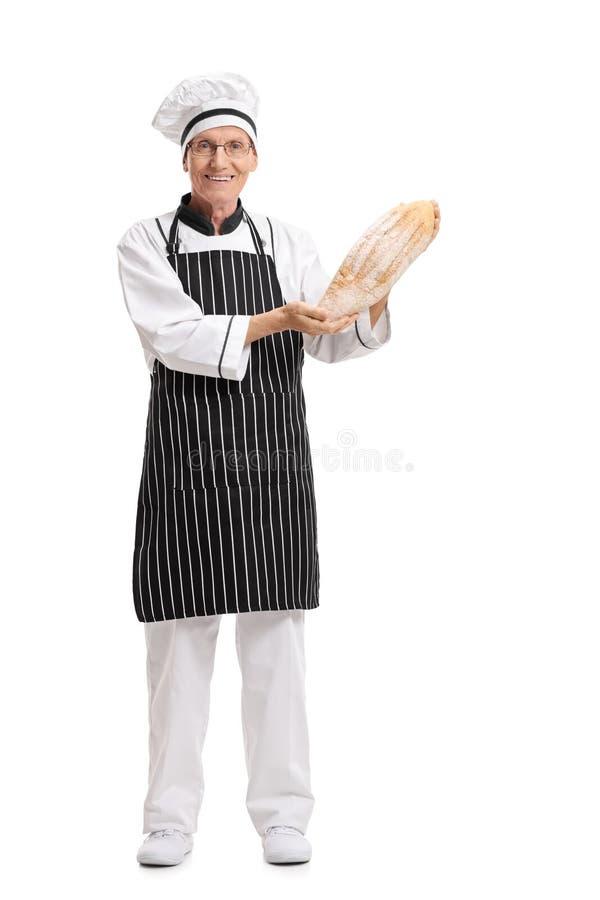 Bagare som rymmer en släntra av bröd fotografering för bildbyråer