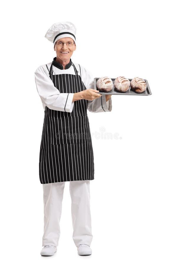 Bagare som rymmer ett magasin med loaves av bröd arkivbild