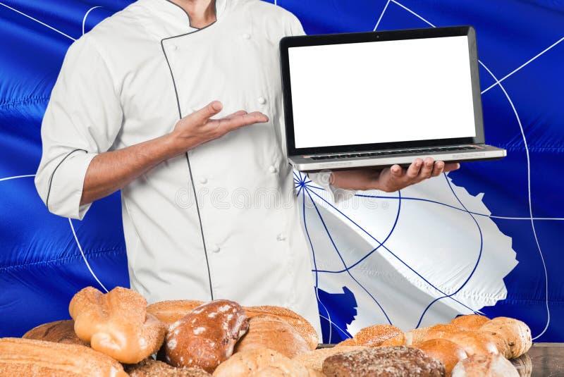 Bagareinnehavbärbar dator på den Antarktis flaggan och brödbakgrund Bärande likformig för kock som pekar den tomma skärmen för ko royaltyfri foto