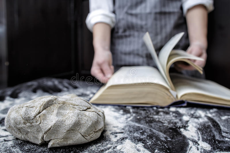 Bagarekock som söker efter ett recept i en kokbok arkivbild