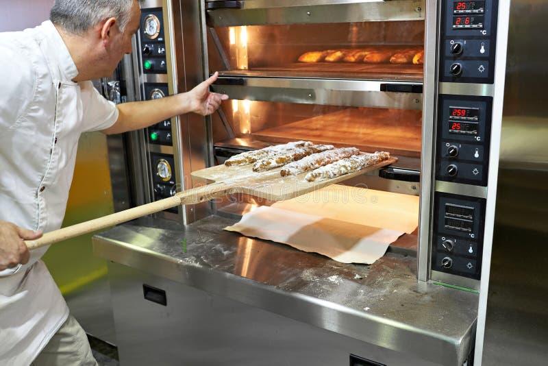 Bagaren bakar bröd i ugn arkivfoton
