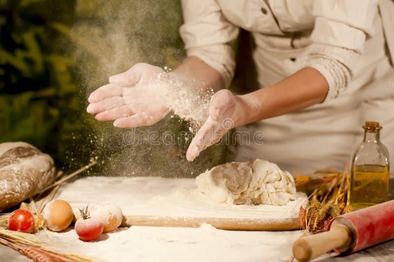 Bagaren för kvinna` s räcker blandning, att knåda förberedelsedeg och framställning av bröd arkivbilder
