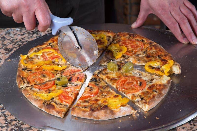 BagareSlicing Fresh Baked vegetarisk pizza med pizzaskäraren fotografering för bildbyråer