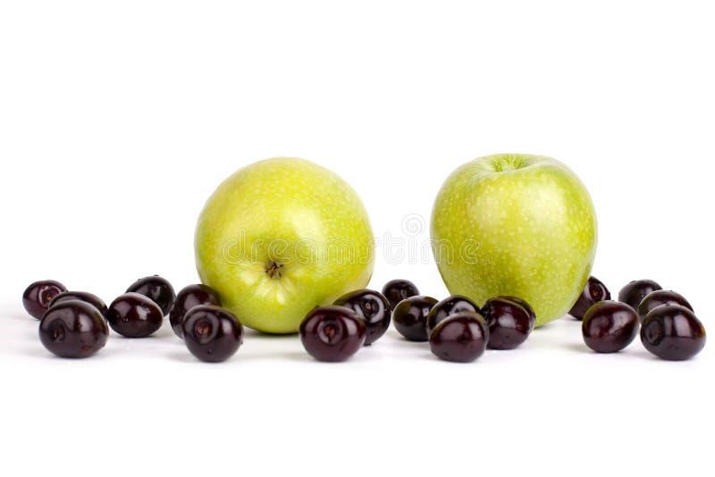 Bagas da cereja e duas maçãs verdes grandes fundo branco no fim isolado acima do macro foto de stock